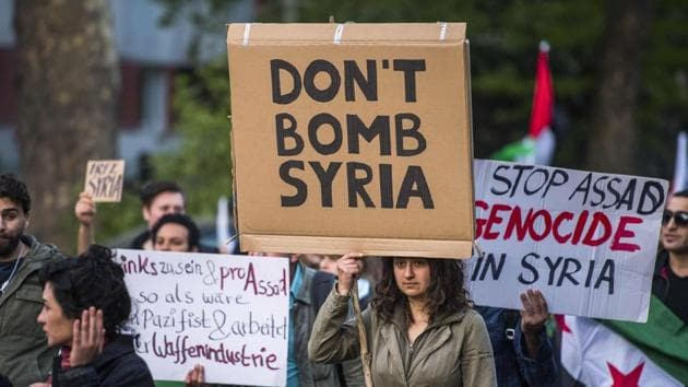 """A demonstrator carries a placard reading: """"don't bomb Syria"""" during the """"Revolutionary 1st of May Demonstration"""" on May 1, 2018 in Berlin.(AFP)"""