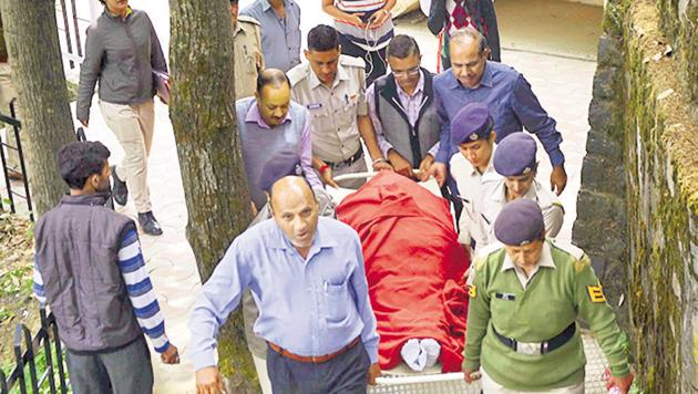 Police carry the body of assistant town planning officer Shail Bala Sharma for a post-mortem examination at the IGMC hospital in Shimla on Wednesday.(PTI Photo)