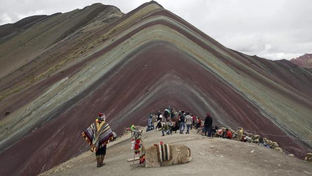 An Andean man rests with his llama on Rainbow Mountain in Pitumarca, Peru.(AP)