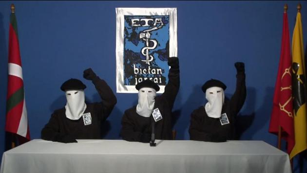 Three ETA militants dressed in black shirts with white hoods and black berets making a declaration from an undisclosed location.(AFP photo)