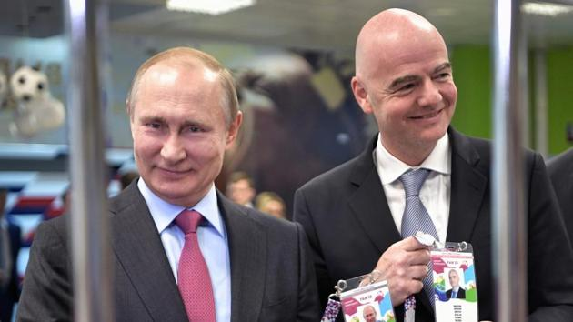 Russian President Vladimir Putin, left, and FIFA president Gianni Infantino show their accreditation cards as they visit the Fisht Stadium in the Black Sea resort of Sochi, Russia, Thursday.(AP)