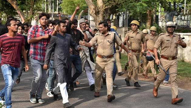 Police tries control the situation after a clash between two groups at Aligarh Muslim University on Wednesday.(PTI Photo)