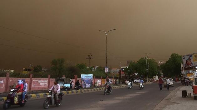 Vehicle ride past on a road during a dust storm in Bikaner on Wednesday.(PTI Photo)