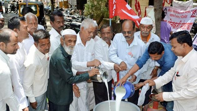 Kisan Sabha activists with farmers distribute milk free of cost to protest the low procurement prices by dairies in the state, in Karad, Maharashtra, on Thursday.(PTI photo)