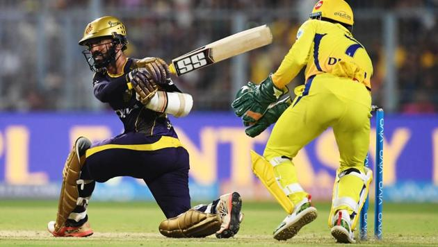 Kolkata Knight Riders (KKR) captain Dinesh Karthik (L) sweeps one to the boundary as Chennai Super Kings (CSK) skipper MS Dhoni looks on during the 2018 Indian Premier League (IPL 2018) match at Eden Gardens in Kolkata on Thursday.(AFP)