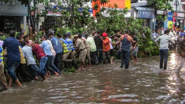 People remove an uprooted tree which had blocked a street, after a thunderstorm in Hyderabad on Thursday. More than 100 people were killed in the freakish pre-monsoon phenomenon that hit UP and Rajasthan the hardest, but also affected many other northern states.(PTI)