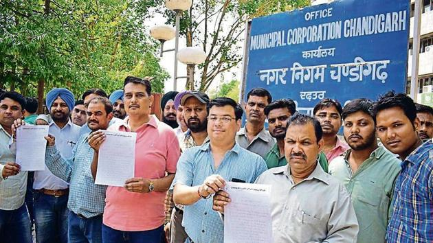 Municipal corporation contractors showing a memorandum they submitted to the MC commissioner, Jitender Yadav, at the civic body's office in Sector 17, Chandigarh, on Friday.(Sikander Singh Chopra/HT)