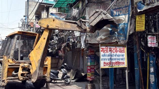 Authorities carry out demolition of illegal structures at Sadar Bazar in New Delhi on Friday.(PTI Photo)