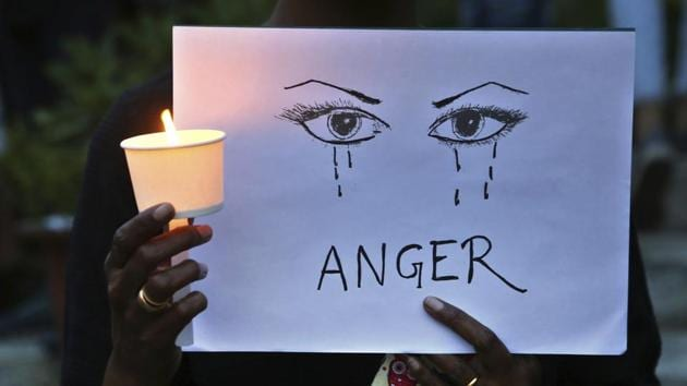 A protester holds a candle and placard seeking an end to sexual violence against women.(AP File Photo)