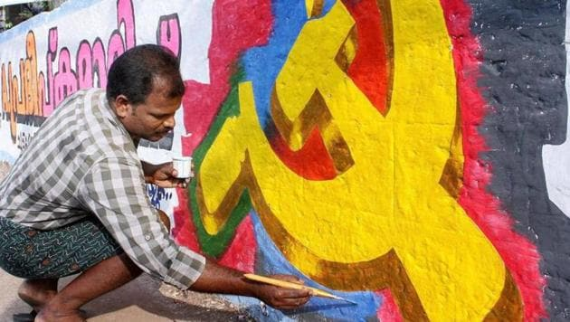 A CPI (M) worker paints a wall for the polls. The ruling CPI(M) has put up its Alappuzha district secretary Saji Cherian against BJP's former state president, PS Sreedharan Pillai and Congress veteran SD Vijayakumar.(PTI/File Photo)