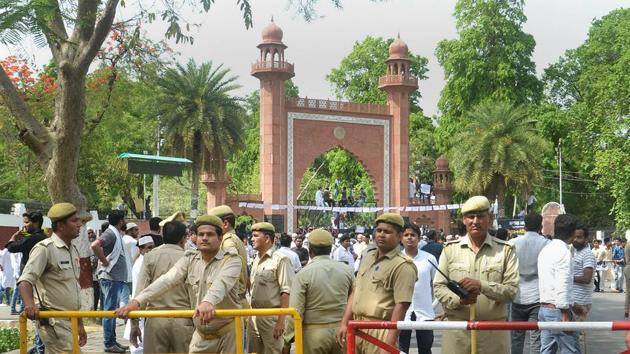 Security personnel stand guard as Aligarh Muslim University students stage a protest over Jinnah portrait issue outside the university gate in Aligarh.(PTI File Photo)