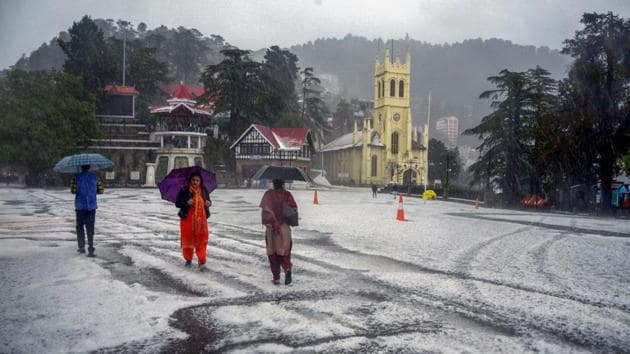People travel during a hailstorm in Shimla on May 8.(PTI Photo)