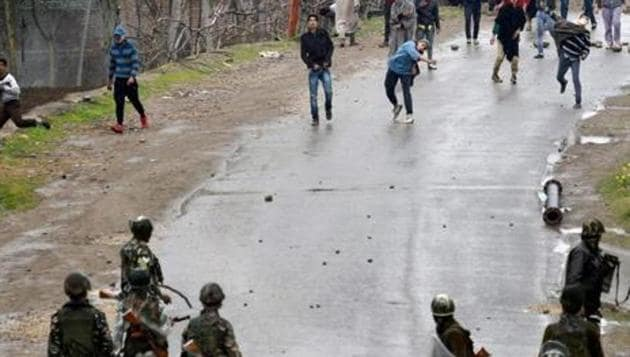 File photo of a group pelting stones at security forces in Budgam district in Kashmir.(PTI)