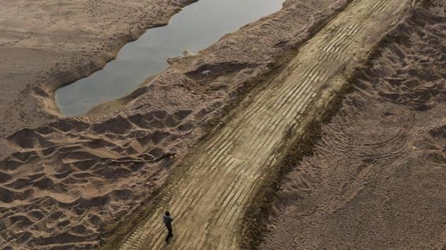 A man walks over truck tire tracks on Ken's rich river bed in Madhya Pradesh.(HT File Photo)