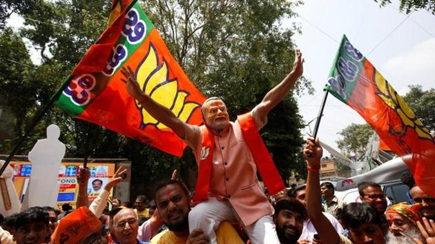 BJP supporters celebrate the party's performance in the Karnataka assembly elections, in Bengaluru on Tuesday.(Reuters)
