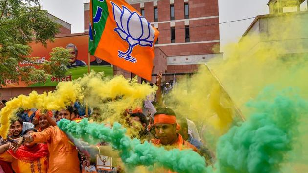 BJP workers celebrate the party's lead during counting of votes for Karnataka Assembly elections.(PTI Photo)
