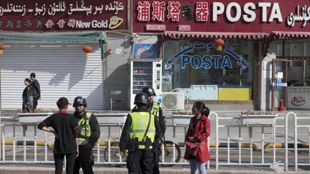 """In this Nov. 3, 2017 photo, residents are seen with security personnel on the streets of Hotan in western China's Xinjiang region. China's """"strike hard"""" campaign in remote Xinjiang is set to intensify in the month of Ramzan with reports saying monitoring of minority Muslim communities in the province had become invasive.(AP Photo)"""