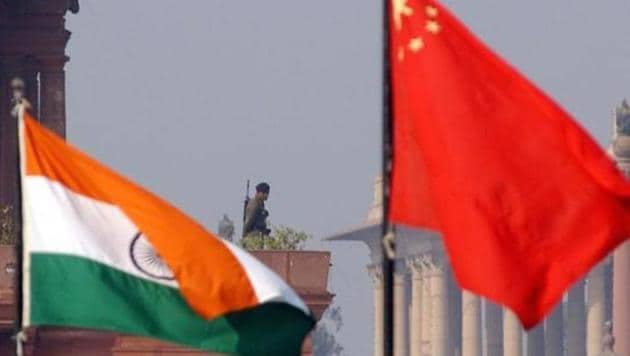 An Indian paramilitary officer is framed by an Indian (L) and Chinese (R) flags as he stands guard near the presidential palace in New Delhi, 12 January 2002.(AFP File Photo)