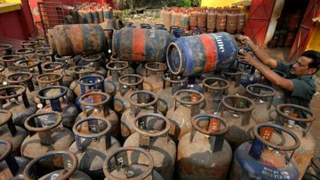A worker arranges empty cooking gas cylinders at a depot in Kolkata. Since the LPG stove is about as costly as the connection, and the fuel several times costlier per year, almost two-thirds of all households given a connection will continue to use or soon revert to mostly using polluting wood.(REUTERS)