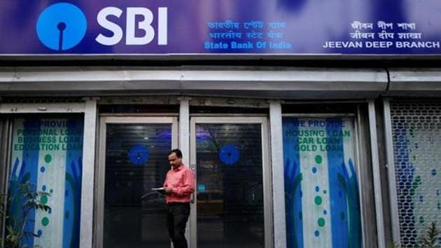 A man checks his mobile phones in front of State Bank of India (SBI) branch in Kolkata, India.(REUTERS File Photo)