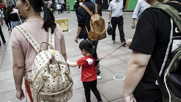 Pedestrians and a child wearing a child harness walks along a pedestrian shopping area in Shanghai, China.(Bloomberg)