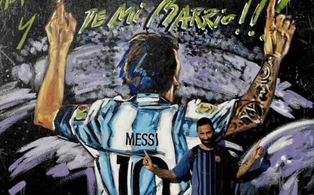 """In this April 18, 2018 photo, Alejandro Daniel Fernandez poses for a photo by a mural of his childhood friend, Lionel Messi, that reads in Spanish """"From my neighborhood!"""" in La Bajada, Rosario, Argentina. Fernandez said Messi's family had always helped him, including living with the family for a while, and that he remains friends with Lionel and his brother who all play soccer together when in town.(AP)"""
