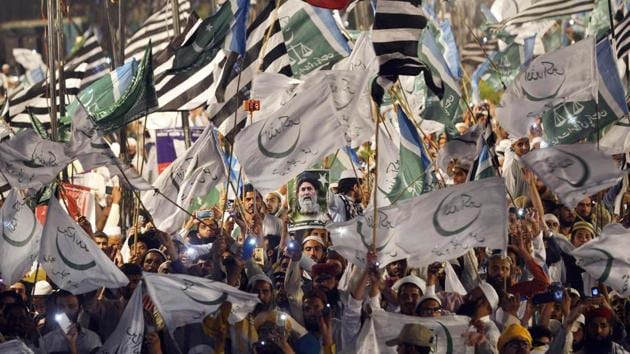 Supporters of Muttahida Majlis-e-Amal (MMA), an alliance of religious parties, waves flags during a public meeting in Lahore on May 13, 2018, ahead of the elections.(AFP)