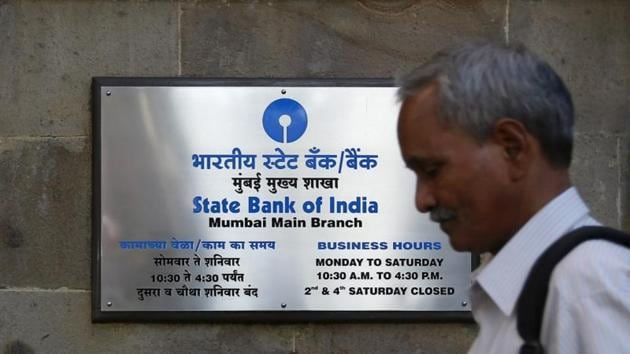 A man walks past the signboard displayed at the State Bank of India main branch in Mumbai.(Reuters File Photo)