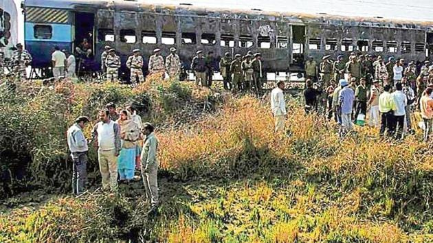 People gather near the burnt bogies of the Samjhauta Express that caught fire following explosions near Panipat in Haryana in 2007.(PTI File Photo)