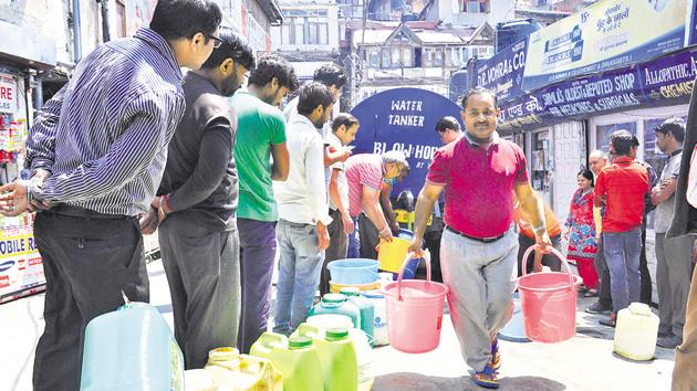 Residents wait in queue to fill buckets and cans with water from a tanker at Lower Bazaar in Shimla on Tuesday.(Deepak Sansta/ HT Photo)
