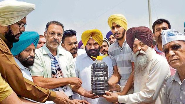 Aam Aadmi Party workers filling bottles with water from Budha Nullah at Gaunspur village in Ludhiana on Wednesday. The bottles were carried in a special vehicle (below) from the nullah.(HT Photo)