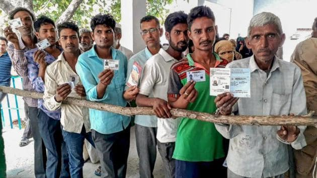 People show their voter IDs as they wait in a queue to cast their vote during Kairana parliamentary constituency re-polls in Shamli on Wednesday.(PTI Photo)