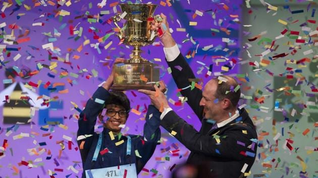Karthik Nemmani, 14, from McKinney, Texas, is presented with the Scripps National Spelling Bee trophy by Adam Symson, president and CEO, E.W. Scripps Company, after he won the bee, in Oxon Hill, Maryland, US, on Thursday.(AP)