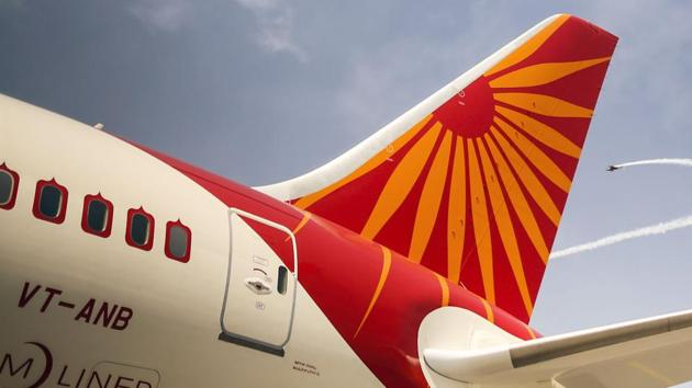 Planes fly past a Boeing Co. 787 Dreamliner aircraft, operated by Air India Ltd. Interested parties balked at the terms when the government made it clear that it didn't wish to sell Air India in parts.(Dhiraj Singh/Bloomberg)