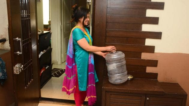 A resident of Brahma Emerald city keeps a 20 litre water can outside her home Since 2009, the society has been receiving 20 litres water cans everyday from the builder for drinking water.(Shankar Narayan/HT PHOTO)