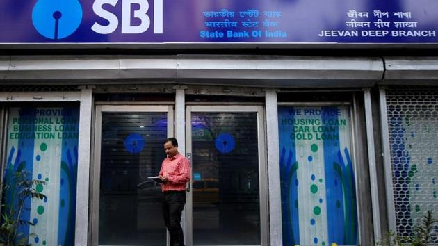 A man checks his mobile phones in front of State Bank of India (SBI) branch in Kolkata, February 9, 2018. The raise of lending rate makes loans costlier for consumers.(Reuters File)