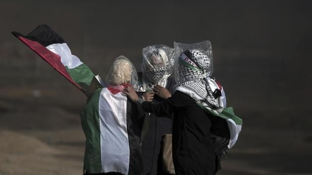 Palestinian women wear plastic bags on their heads as a protection from teargas during a protest at the Gaza Strip's border with Israel, Friday, June 1, 2018.(AP Photo)