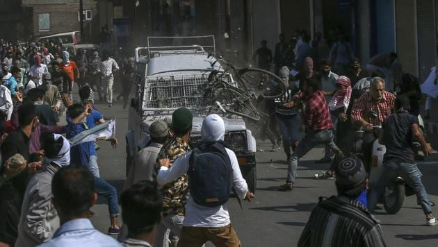 Protesters throw rocks, bricks and a cycle on a CRPF jeep in Srinagar on June 1, 2018. Two people were injured after the vehicle ran over them.(AP)