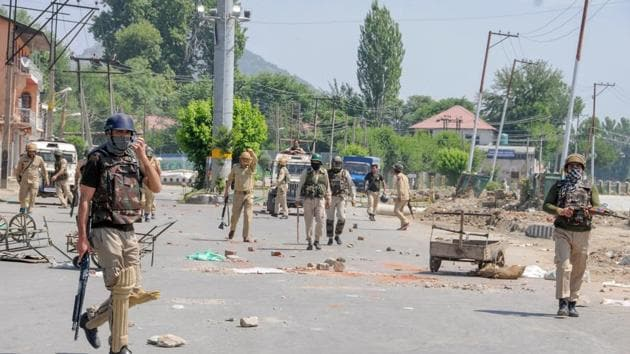 Security personnel patrol a deserted street during a curfew imposed to maintain law and order in Srinagar.(PTI Photo)
