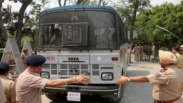Police officers gesture as a vehicle carrying accused in the rape and murder of an eight-year-old girl in Kathua, near Jammu, enters a court premises in Pathankot, Punjab, on May 31, 2018.(Reuters File Photo)
