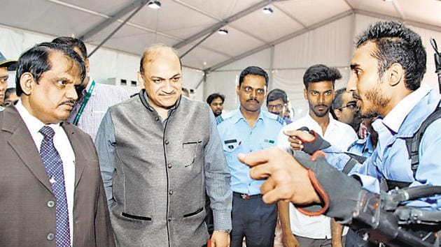 Bhushan Darekar, COEP student (right), explaining the working of the compressed air powered human exoskeleton to S Christopher, chairman, DRDO (left) and PK Mehta (2nd from left), director general, armament and combat engineering systems, DRDO.(HT PHOTO)