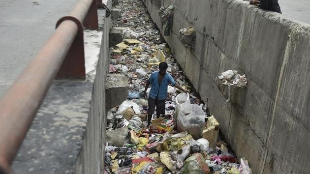 A man scavenges through a drain full of discarded plastic at Geeta colony in Delhi. As Delhi observes yet another World Environment Day, it is yet to get its act together when it comes to handling solid waste.(Ravi Choudhary/HT File Photo)