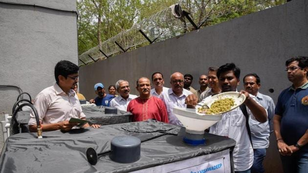 Alumni of BMCC inaugurate the machine which can convert waste food into biogas at the college on Monday.(SANKET WANKHADE/HT PHOTO)