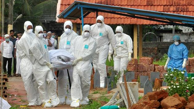 Doctors and relatives wearing protective gear carry the body of a Nipah virus victim during his funeral at a burial ground in Kozhikode, on May 24, 2018.(Reuters)