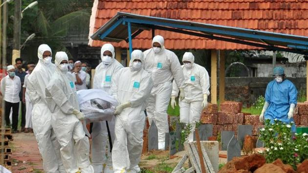 Doctors and relatives wearing protective gear carry the body of a victim, who lost his battle against the brain-damaging Nipah virus, during his funeral at a burial ground in Kozhikode, Kerala.(HT PHOTO)