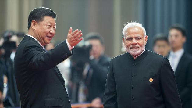 Chinese President Xi Jinping, left, welcomes Prime Minister Narendra Modi for a meeting at the Shanghai Cooperation Organisation (SCO) Summit in Qingdao in eastern China's Shandong Province on Sunday.(AP Photo)