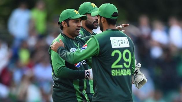 Pakistan skipper Sarfraz Ahmed (L) celebrates with Shadab Khan following the first Twenty20 International cricket match between Scotland and Pakistan at the Grange Cricket Club in Edinburgh, Scotland, on June 12, 2018. Pakistan won the match by 48 runs.(AFP)