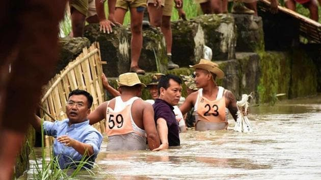 Flood control secretary, Deleep Singh (in blue shirt), is seen helping flood victims in waist-deep water.(Twitter)