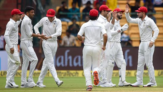 Afghanistan bowler Yamin Ahmadzai celebrates with teammates the wicket of India's Shikhar Dhawan during their one-off Test at Chinnaswamy Stadium in Bengaluru on Thursday.(PTI)