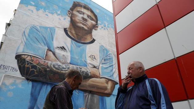 Flags bearing Lionel Messi's face hang over barriers, while a giant mural of the Barcelona star towers above the people of Bronnitsy as they come to terms with the intense spotlight now fixated on their hometown.(AP)